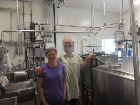 Amy and Paul pose by the bulk tank