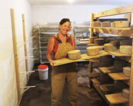 Maryrose shows off some of her tomme cheeses.