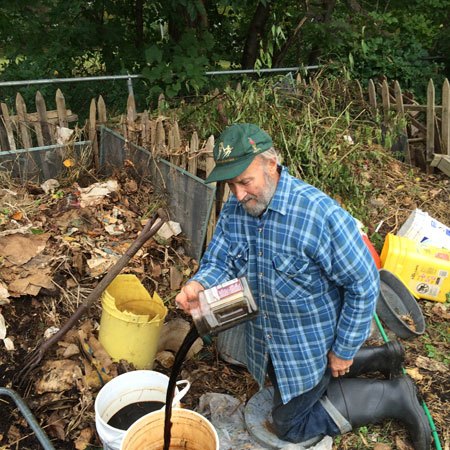 Here Gersitz pours leachate from the sump bucket into a pail to transfer to one of his rain barrels for dilution.