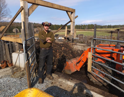 Tom poses on the ramp by the bin. At the left hens wait for access, on the right is the tractor Tom uses to move material from the bin every month to compost piles (one of which you can see just beyond the tractor exhaust pipe).