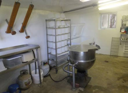 The cheese room has cheese presses, shown on upper left hanging from the ceiling,  cheese molds on the shelves, the vat in which the milk is heated,  and a freezer made into a milk cooler.