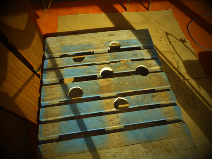 photo by Jack Kittredge The pipe holes have now been cut in the pallet. Notice how their placement has avoided totally bisecting the center 4x4 supporting the boards forming the top of the pallet.