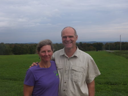 photo by Jack Kittredge Amy Klippenstein and Paul Lacinski on their scenic Hawley dairy farm, showing views of New Hampshire behind them.