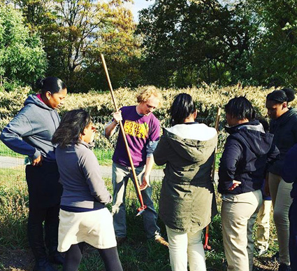 Food Corps member, Alex Stenner, demonstrates tools at Costello Urban Farm