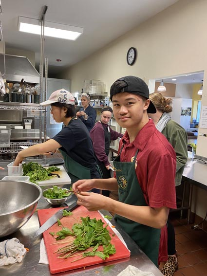Teen volunteers in Ceres kitchen preparing meals