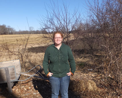 Laura Sackton, owner of First Root Farm, with one of her fields behind her