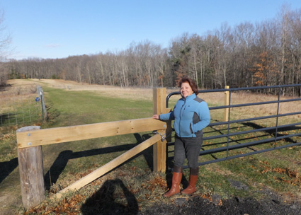 Lucy McCain beams as she shows off the town conservation land where her goats browse. She has a key to the locked gate so she can get her vehicle down to the pastures  that are fenced off on both sides of the central aisle.