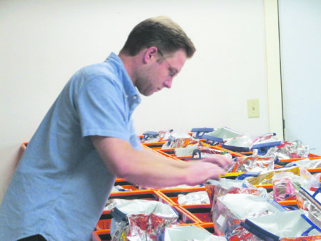 Teddy Gamache fills home delivery baskets for the Hub's customers.