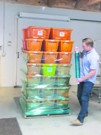 Teddy Gamache wraps home delivery baskets for storage in the cooler until the truck returns to pick them up