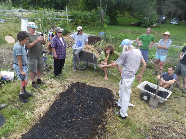 David Yarrow spreads biochar from white cart onto a garden bed he is preparing in Colrain, Massachusetts. The biochar was produced the day before in a homemade burner.