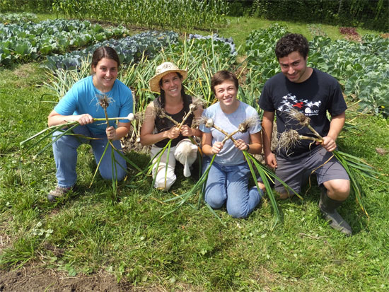 Members of the garden crew, Allyson, crew chief Lisa, Melissa and Benjamin show off the garlic they have raised at the ranch.